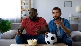 Multi-etnische kerels die op voetbalwedstrijd letten, die door nederlaag van favoriet team wordt gefrustreerd royalty-vrije stock afbeeldingen