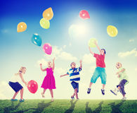 Multi-etnische Kinderen die in openlucht Ballons samen spelen Royalty-vrije Stock Foto