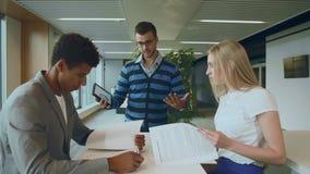 Multi-etnische medewerkers met documenten en tablet Zijaanzicht van de zwarte mens met medewerkers bij lijstlezing documenten en  stock videobeelden