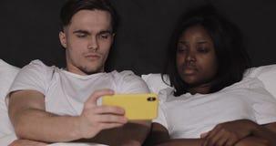 Multi-etnische paar het letten op video samen op gele smartphone die in bed bij nacht liggen stock video
