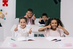 Multi-etnische schoolkinderen die duimen tonen terwijl het zitten bij bureaus in klaslokaal stock afbeeldingen
