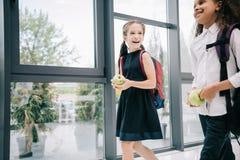 Multi-etnische schoolmeisjes die appelen houden terwijl het lopen in schoolgang Royalty-vrije Stock Foto