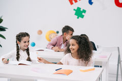 Multi-etnische schoolmeisjes die elkaar glimlachen terwijl schooljongens die erachter in klaslokaal spreken Stock Afbeeldingen