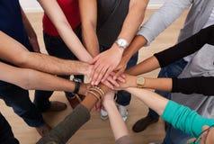 Multi-etnische studenten die handen stapelen Stock Afbeeldingen