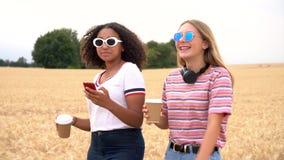 Multi etnische tiener jonge vrouwen die zonnebril dragen die koffie drinken en selfies op hun smartphones voor sociale media neme stock videobeelden