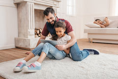 Multi-etnische vader en dochter die digitale tablet op tapijt thuis gebruiken Stock Afbeelding