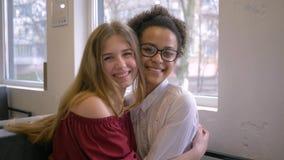 Multi-etnische verhouding, gelukkig Afrikaans Amerikaans tienermeisje die meisje omhelzen en in koffie glimlachen stock footage