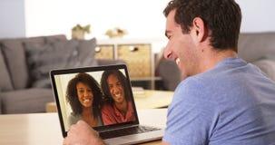Multi-etnische vrienden die op laptop webcamming Stock Afbeeldingen