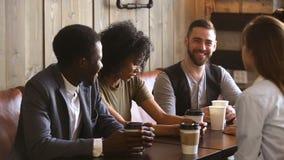 Multi-etnische vrienden die samen drinkend koffievergadering in comfortabele coffeeshop genieten van stock videobeelden
