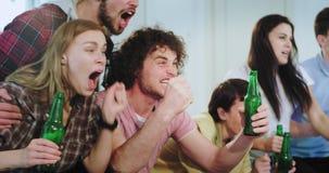 Multi etnische vrienden die thuis op voetbalwedstrijd voor TV letten wekten zij zeer het vieren van de overwinning van hun op stock footage