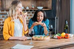 Multi-etnische vrouwen die pizza thuis eten en wijn drinken Royalty-vrije Stock Foto