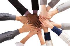 Multi executivos étnicos que empilham as mãos imagem de stock
