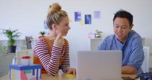 Multi executivos empresariais étnicos novos que trabalham no portátil no escritório 4k filme