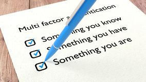 Multi factor authentication checklist with a pen. Cybersecurity checklist with a blue ballpen setting a tick in all three multifactor authentication checkboxes Stock Photos