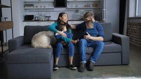 Multi família étnica com o cão que relaxa no sofá filme