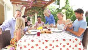 Multi família da geração que aprecia a refeição exterior junto vídeos de arquivo