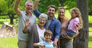 Multi família da geração que sorri e que acena na câmera em um parque filme