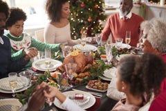 Multi família da raça misturada da geração que senta-se na tabela de jantar do Natal que guarda as mãos e que diz a benevolência, fotografia de stock