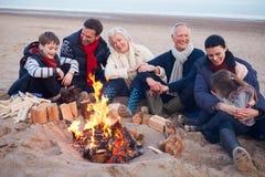 Multi famiglia della generazione che si siede dal fuoco sulla spiaggia di inverno fotografia stock libera da diritti