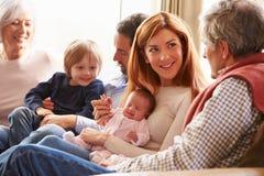 Multi famiglia della generazione che si siede su Sofa With Newborn Baby Fotografia Stock