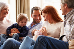 Multi famiglia della generazione che si siede su Sofa With Newborn Baby Fotografie Stock Libere da Diritti