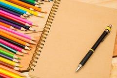 Multi farbige Bleistifte, Bleistift und Notizbuch mit Text-Raum Lizenzfreies Stockfoto