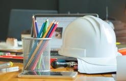 Multi farbige Bleistifte im Kasten mit Schutzhelm, intelligentem Telefon und Lizenzfreies Stockfoto