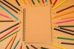 Multi farbige Bleistifte und Notizbuch mit Text-Raum Lizenzfreies Stockfoto