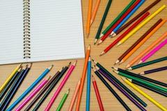 Multi farbige Bleistifte und Notizbuch mit Text-Raum Lizenzfreie Stockbilder