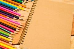 Multi farbige Bleistifte und Notizbuch mit Text-Raum Stockfotografie