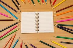 Multi farbige Bleistifte und Notizbuch mit Text-Raum Lizenzfreie Stockfotografie