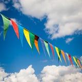 Multi farbige dreieckige Flaggen auf Hintergrund des blauen Himmels Lizenzfreies Stockbild