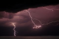 Multi Flash Storm. A stream of lightning bolts erupts from a thunder cloud over Lake Michigan Royalty Free Stock Photos