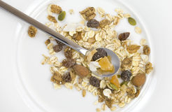 Multi fruit and nut muesli. Arranged with silver spoon on white plate Stock Photos