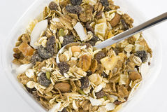 Multi fruit and nut muesli. With silver spoon arranged in plastic box and isolated on white background Royalty Free Stock Image