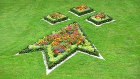 Multi gekleurde bloembedden in speciale vormen met het omringen van gazon stock fotografie