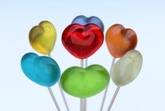 Multi gekleurde hartvorm lollypops stock foto's