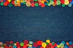 Multi gekleurde knopen aan de kant van een achtergrond van de denimstof stock afbeelding