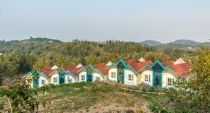 Multi gekleurde rijtjeshuizen bovenop een heuvelpost met berg op de achtergrond, Salem, Yercaud, tamilnadu, India, 29 April 2017 royalty-vrije stock foto