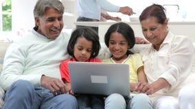 Multi-Generation ινδική οικογένεια με τη συνεδρίαση lap-top στον καναπέ φιλμ μικρού μήκους