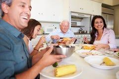 Multi-Generation οικογενειακή συνεδρίαση γύρω από τον πίνακα που τρώει το γεύμα στοκ εικόνα