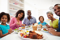 Multi Generation African American Family Eating Meal At Home. Looking To Camera Smiling Royalty Free Stock Photo