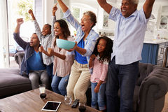 Multi generation black family watching sport on TV celebrate Royalty Free Stock Images