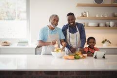 Multi-generation familj som förbereder mat i kök arkivbilder