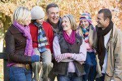 Multi-generation family on autumn walk. Sitting on fence Stock Photography