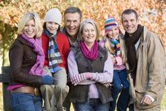 Multi-generation family on autumn walk. Sitting on fence Stock Image