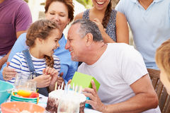 Multi Generation Family Celebrating Birthday In Garden Stock Image