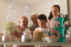 Multi-generation family celebrating birthday of grandson. Front view of a multi-generation family celebrating birthday of grandson with a birthday cake at home stock photo