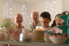 Multi-generation family celebrating birthday of grandson. Front view of a multi-generation family celebrating birthday of grandson with a birthday cake at home stock photography
