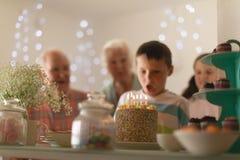 Multi-generation family celebrating birthday of grandson. Front view of a multi-generation family celebrating birthday of grandson with a birthday cake at home stock images